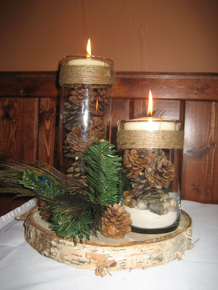 Centerpieces were a large birch slab with two cylinder vases with sand river rock pinecones and candle with twine around the top. then a bit of evergreen pinecones and peacock feathers around the vases,