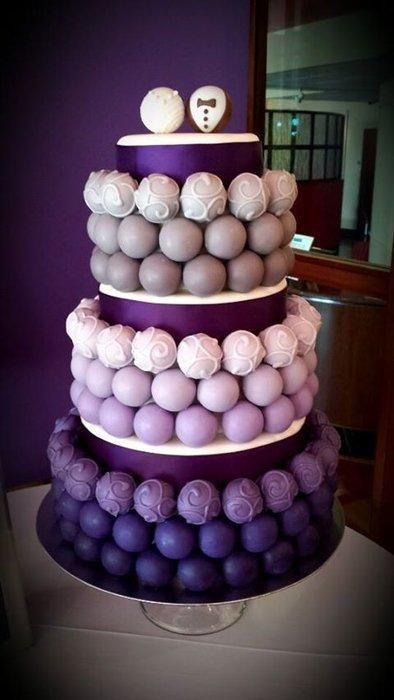 This cake bite cake was made for a purple and gray wedding. The bottom tier cake bites are lemon, the middle tier Italian cream and the top tier was German chocolate. The cake is topped off with a bride and groom cake bite.