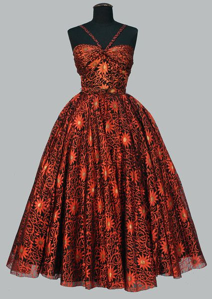 TRAINA NORELL VOIDED SILK BALL GOWN, 1950's. Overall pattern of copper daisies with gold metallic centers and serpentine foliage outlined on black organza having boned sweatheart bodice ruched at center of bust by a narrow strap, full skirt over black crinoline, narrow bodice lined in black taffeta, back zipper.