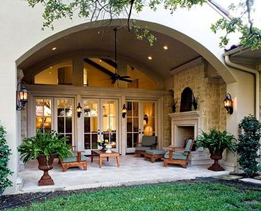 outdoor room with arched opening and wall of french doors, fireplace...