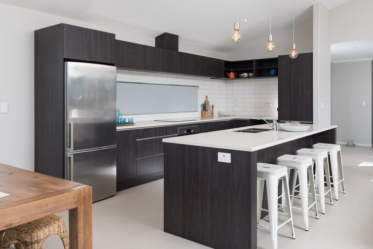 This G.J. kitchen features a large kitchen island  with the main kitchen having a funky white tiling splash back. The blind is down covering a window that can see out to the backyard.