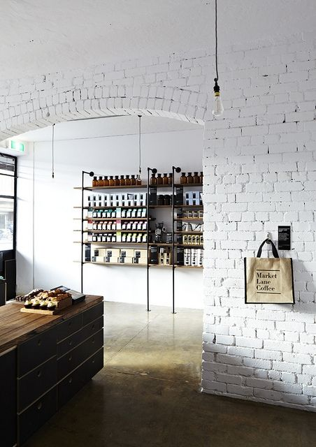 Exposed brick wall painted white, concrete floor, aged wood and industrial minimal shelves and table.