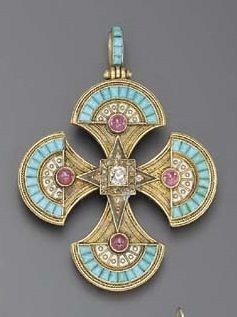 AN EGYPTIAN REVIVAL DIAMOND, RUBY, ENAMEL AND GOLD PENDANT. Centring upon an old mine-cut diamond, within an old mine-cut diamond surround, enhanced at the cardinal points by cabochon rubies, white enamel and calibré-cut turquoise trim, further accented by gold wirework detail, suspended from a calibré-cut turquoise bail, the reverse set with four glass covered hair compartments, circa 1865