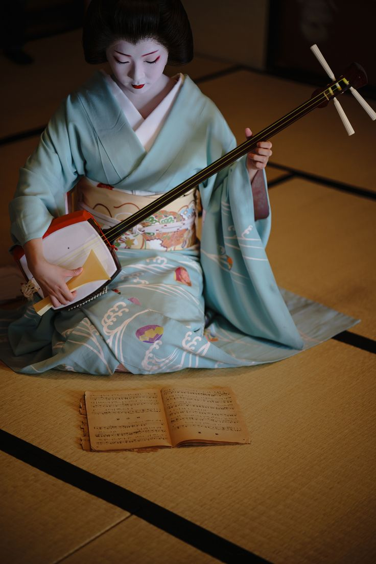 Toshimana playing the shamisen More