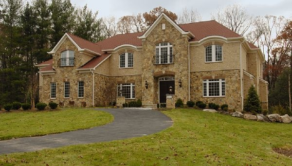 Luxury custom home with a brick and stone exterior for Custom brick homes
