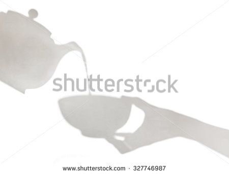 Delicate shadows of teapot pouring liquid into a cup held by female hand. Shadow play.
