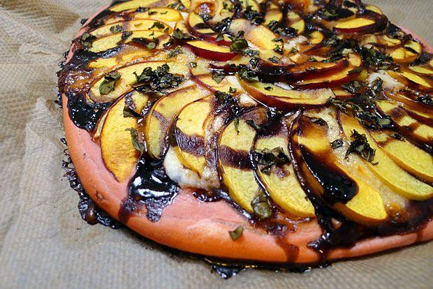 Rosa Pizza mit Pfirsichen, Mozzarella und (optional) Putenbrust. Der Teig ist ausschließlich mit roter Beete gefärbt, die jedoch geschmacksneutral ist.