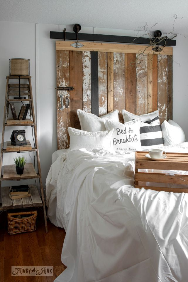 A cheater reclaimed wood barn door headboard with faux hardware, with a Bed & Breakfast DIY pillow, made with Funky Junk's Old Sign Stencils | funkyjunkinteriors.net