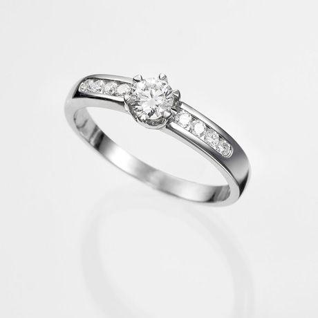 Anillo solitario de diamantes CEIBA  Anillo solitario con diamante central talla brillante engastado en una montura de oro de 18 kilates en seis garras con 8 diamantes talla brillante de 0,25 quilates en los brazos.