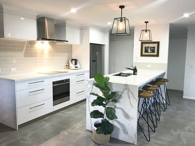 Brisbane Builder eclat building co. kitchen renovation. This light, industrial and modern kitchen features marble benchtop, concrete tile flooring, white cabinetery, pendant lights, timber and steel bar stools and grey subway tile splashback