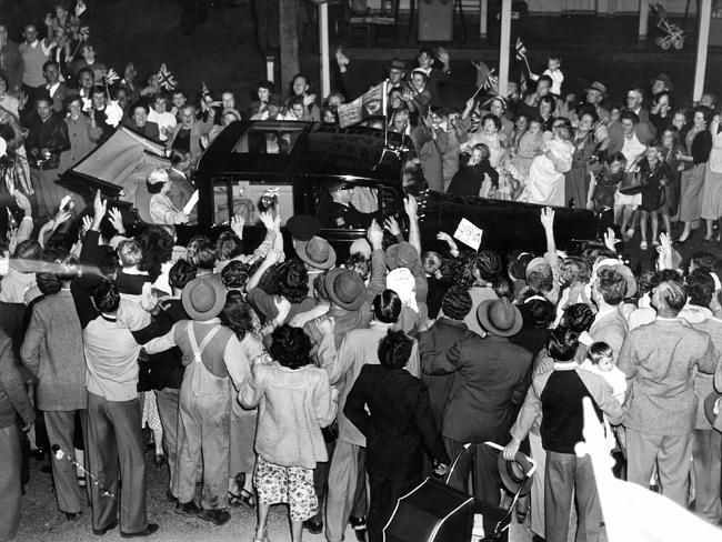 Crowds rush the car containing the Queen as it heads down the road at Gepps Cross in 1954