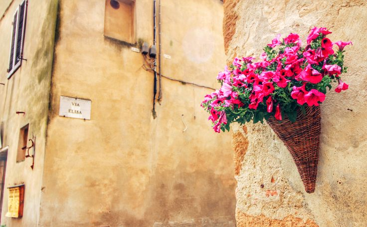 """Old buildings in Pienza are decorated with colorful flowers :) And between 1st and 10th of May there is a flower and plant fair which is held every year. The central market in Pienza, Piazza Pio II is completely invaded by flowers and it looks simply amazing. This is indeed the """"ideal city"""", as Pope Pius II wished to create. Because initially, Pienza was just a small village (called Corsignano) but Pope Pius II transformed it into a classical Renaissance ideal city. He did a great job! :)"""