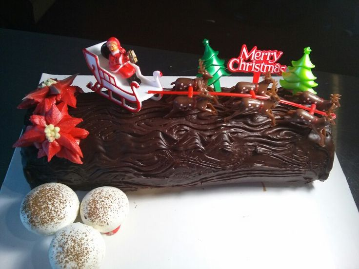 Buche de Noel. Chocolate sponge cake filled with whipped cream and covered in chocolate ganache. Buttercream poinsettias and meringue mushrooms.