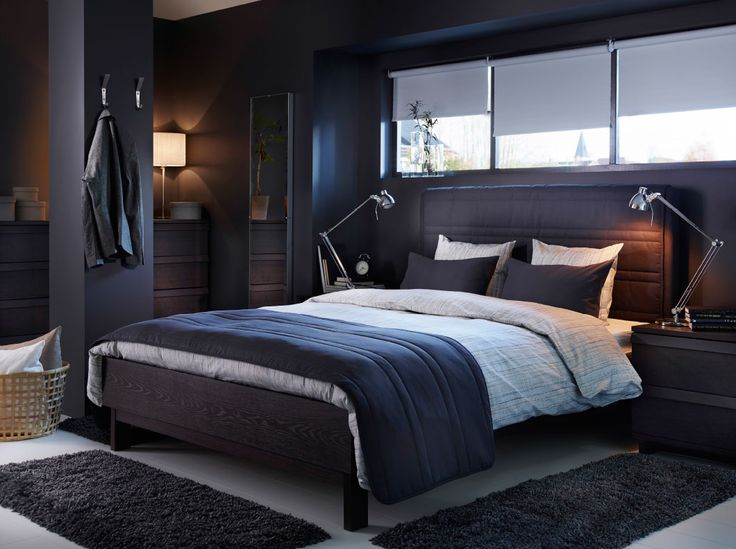 A dark grey bed with fabric headboard and bedtextiles in beige and dark grey. **I like the way the bed is made!**