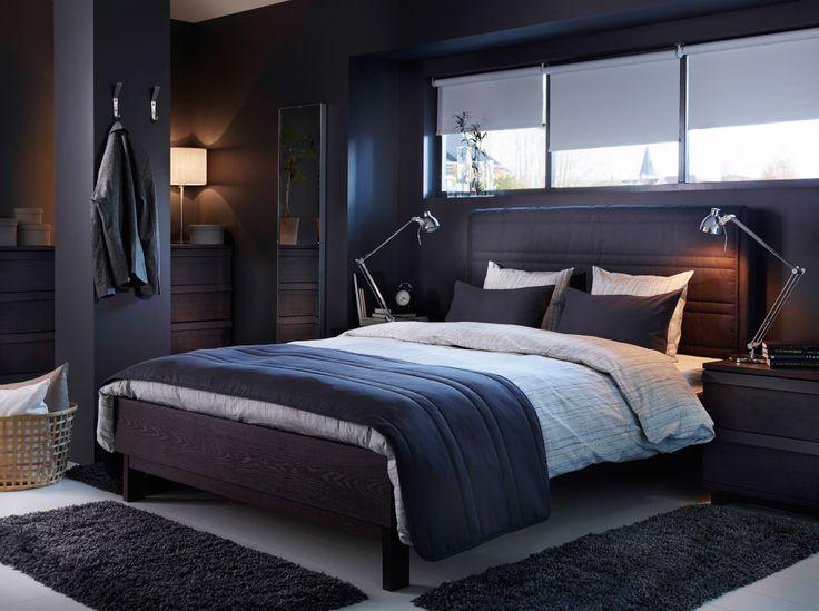 Mörkgrå säng med huvudgavel i tyg och bäddtextilier i beige och mörkgrått.