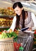 Obraz Pretty Woman produktów wybierając w supermarkecie z listą rzeczy do kupna stock photography