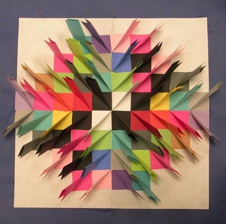 """Large white paper is cut 11"""" x 17"""" Great project to do towards the end of the school year to use up odd sizes of construction paper. Cut paper 3"""" x 3"""". fold the white paper in half one way, open up, fold the other way, and open flat. """"invisible"""" starting point. The colored 3"""" x 3"""" paper is folded in half and then at one small end, fold it towards the folded middle, like making a point on a paper airplane. Fold it back so there is a flap that can be glued down along the invisible line."""