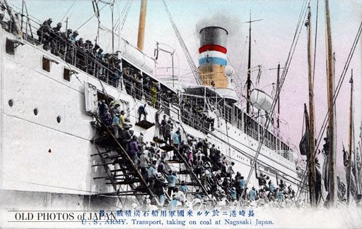 A crowd of harbor workers load high quality Kyushu coal onto a US army transport ship in Nagasaki. As soon as ships entered Nagasaki Harbor, hundreds of men, women, girls and boys swarmed around them on coal barges, built temporary structures, and started to load the hungry ships with coal.    The spectacle was popular entertainment for the passengers.