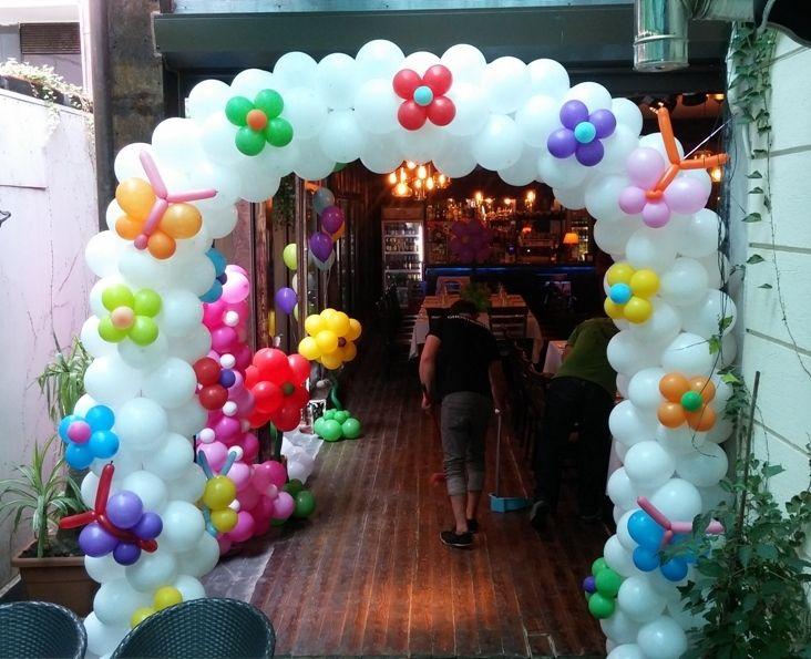 Arcada din baloane albe cu floricele si fluturasi multicolori aplicati.