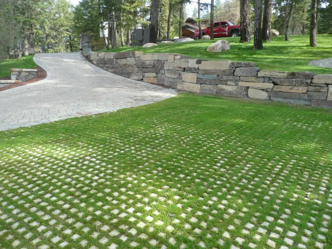 Paver driveway with grass grid pavers and boulder wall constructed of ledge…