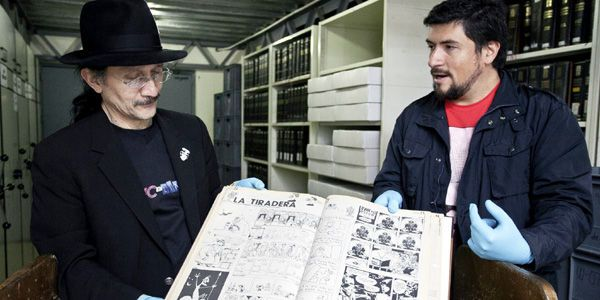 Los historietistas Bernardo Rincón y Pablo Guerra revisan la historia del cómic en la prensa bogotana, en los depósitos de la Biblioteca Nacional. En sus manos, un ejemplar de La Tiradera.