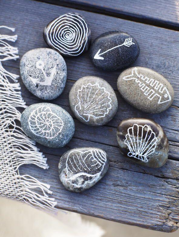 pintando con rotulador planco sobre piedras.
