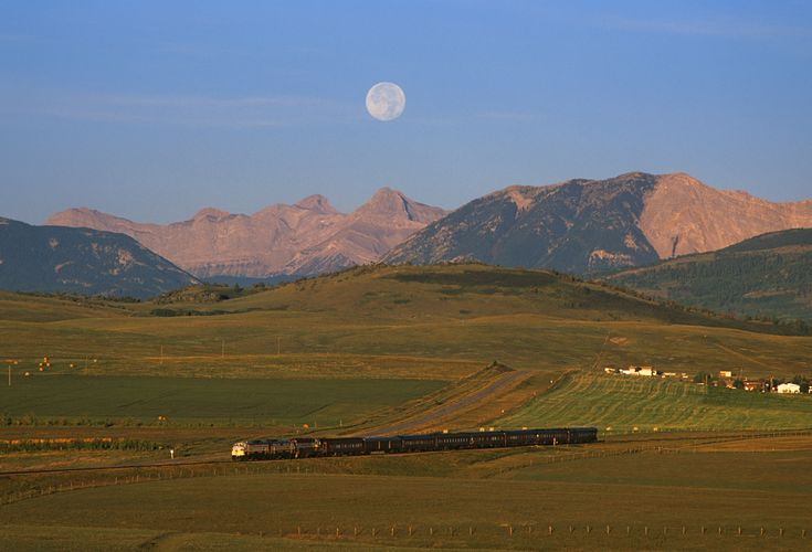 The moon sets over the Canadian Rockies at sunrise, on September 22, 2002. It's a new day as the Royal Canadian Pacific excursion train, heads east at Lundbreck Alberta, Canada ~ Photo by...Mike Danneman©