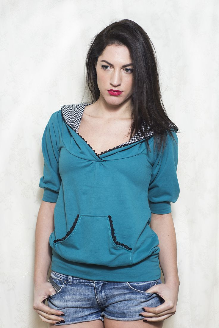 Short sleeved sweater blouse with middle pocket. Teal (blue/green) colour contrasts with black and white gingham hood lining. Casual spring hoodie with discreet black cotton lace detail all round the hood and pocket.