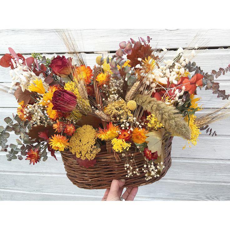cesta-de-mimbre-decorada-con-flores-secas-en-tonos-naranjas-y-amarillos-rosas-secas-y-eucalipto-preservado