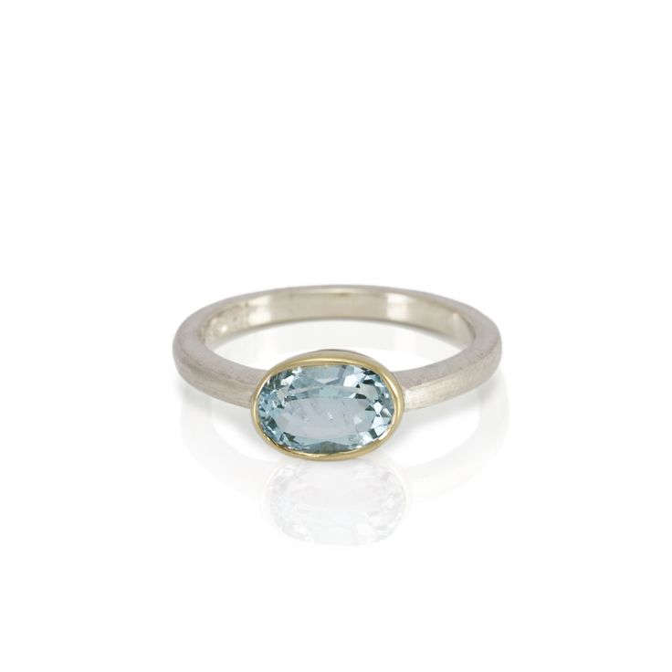 Nefertiti Blue Aquamarine Engagement Ring  Hand-made in 9 carat white gold and 18 carat yellow gold, with oval faceted Blue Aquamarine solitaire (8×6 mm).