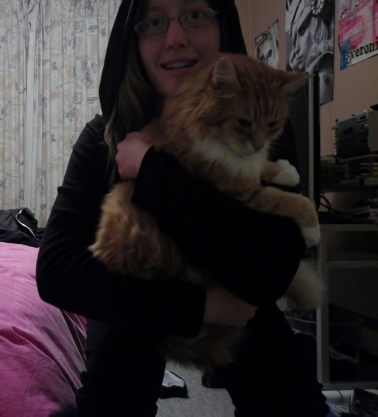 Malice squats with one uninterested cat. Note she is wearing a cat onesy!