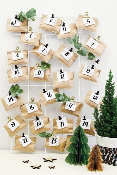 Homemade Advent Calendars For Kids. Mini brown paper parcels and monochrome labels clipped to wire notice board.