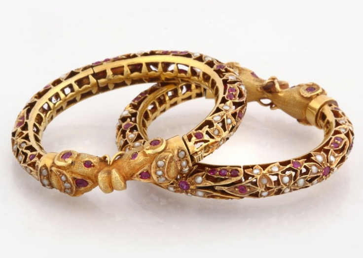 A PAIR OF RUBY AND PEARL 'KADA' BANGLES Each of openwork design, kundan-set with rubies and pearls, the similarly-set finials designed as stylized elephant heads, with a total gemstone weight of approximately 14.00 carats, and a total pearl weight of approximately 1.50 grams, mounted in gold. Diameter: 3.70 cms (1.50 inch)