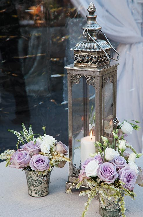 An ornate silver lantern was arranged with mercury vases of lavender and white roses.