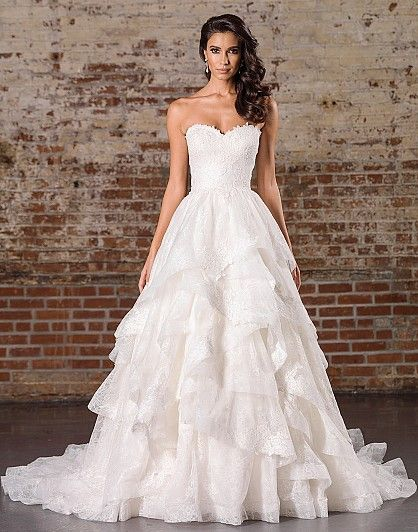 A voluminous ball gown skirt meets soft styling in this gown with a sweetheart neckline, natural waistline, allover lace details, and a tiered skirt.