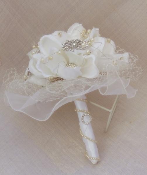 Este Ramo de Novia cuenta con elegantes flores de magnolia, Broches de perlas y strass .Se termina con un mango de raso en color blanco roto acompa...