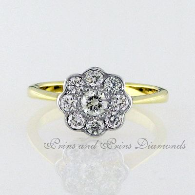 There are 9 = 0.58ct  GH/VS – SI round brilliant cut diamonds tube and pavé set in a white gold cluster setting with an 18k yellow gold shank