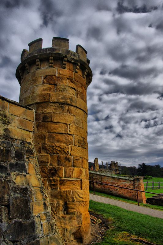 The guard tower in the Port Arthur penal settlement ruins.  Port Arthur was first settled in 1830 as a timber town, however its deep port and remoteness soon saw the town develop into a timber harvesting penal colony. The hardest criminals were sent here to serve their sentences with hard labour. It served as a major prison from 1833 to 1877 when it closed. The buildings were abandoned and large bushfires in 1895 and 1897 further reduced the number of surviving buildings. In 1979 funding was…
