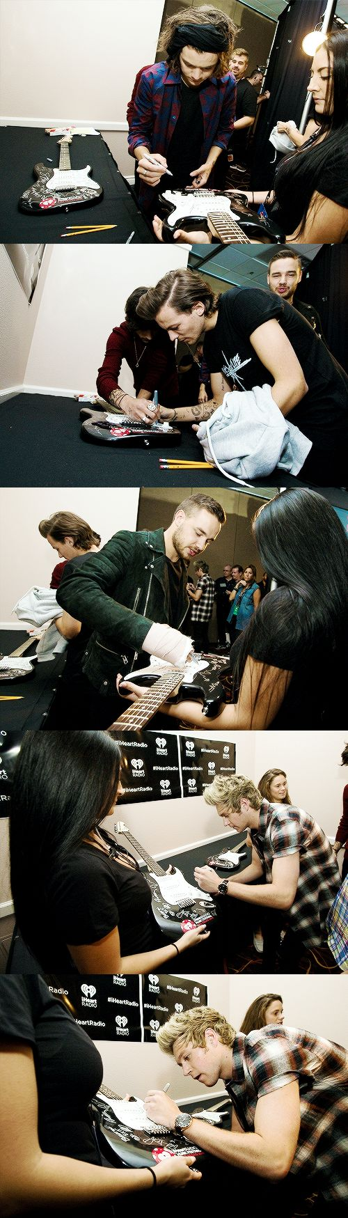 The boys signing a guitar backstage at the iheart radio festival. Poor Liam trying to sign with his cast.lol. 9.20.14