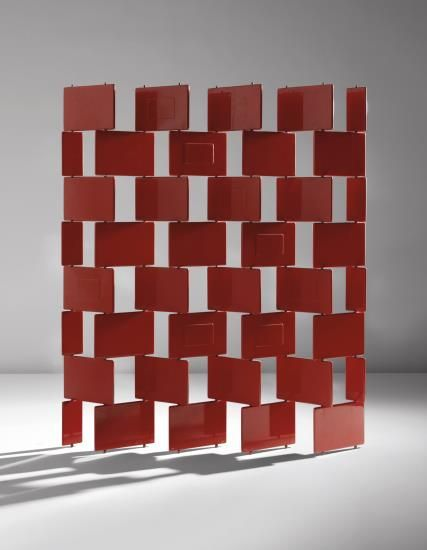 "EILEEN GRAY Unique ""Brick"" screen designed 1922-1923, executed 1973 Red lacquered wood, steel, brass. Each large brick: 8 5/8 x 12 5/8 x 1/2 in. (21.9 x 32.1 x 1.3 cm) 71 1/4 in. (181 cm) high Variable width, as shown: 59 in. (149.9 cm) Lacquer executed by Pierre Bobot, Paris."