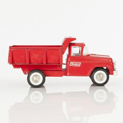 "Red steel toy truck with hydraulic dumper and spring suspension. Buddy ""L\"" produced robust and iconic versions of working class utility vehicles and are now highly collectable."