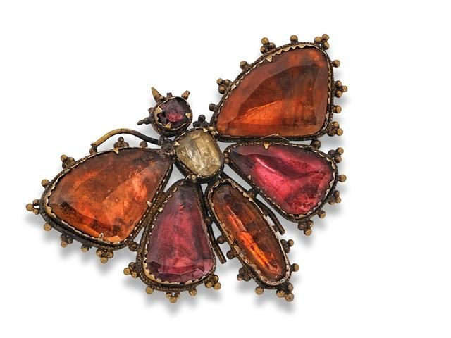 A Georgian gem-set butterfly brooch, circa 1800 The body and wings set throughout with vari-shaped quartzes, the head with a cushion-cut garnet, all to closed-back foiled settings, width 47mm.