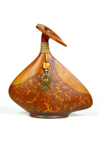 Jarrón fabricado en madera tallada con dibujo de flores. Color marrón. Decorado con colgante y cuero. Estilo moderno.  Decora el mueble auxiliar, mesa de centro, entrada, recibidor... Envío en 24h.