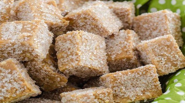 250g de Amendoim  torrado;  - 1 pacote e meio de bolacha maisena;  - 01 lata de leite condensado;  - 1 colher (sopa) de chocolate em pó;  - Açúcar cristal para cobrir.