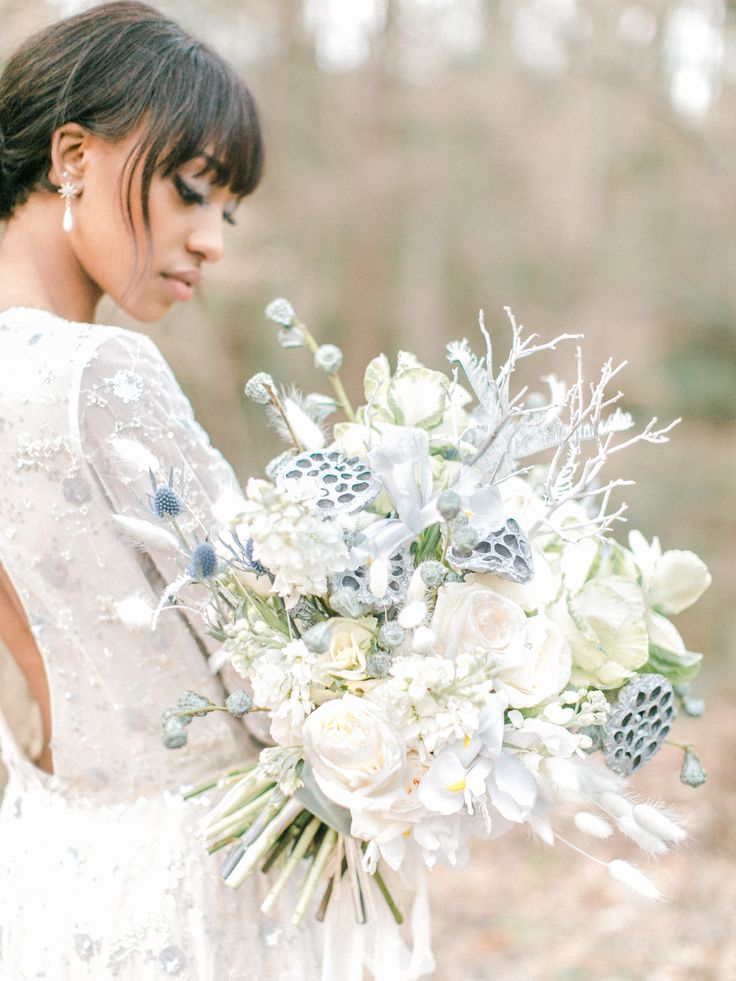 A luxury winter white bridal bouquet of iris, lotus, white o'hara, thistle, bunny tails, and kale