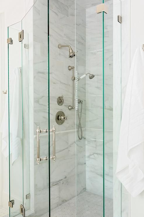 Glass shower doors frame a stand-up shower in a transitional bathroom with large marble staggered tiles.