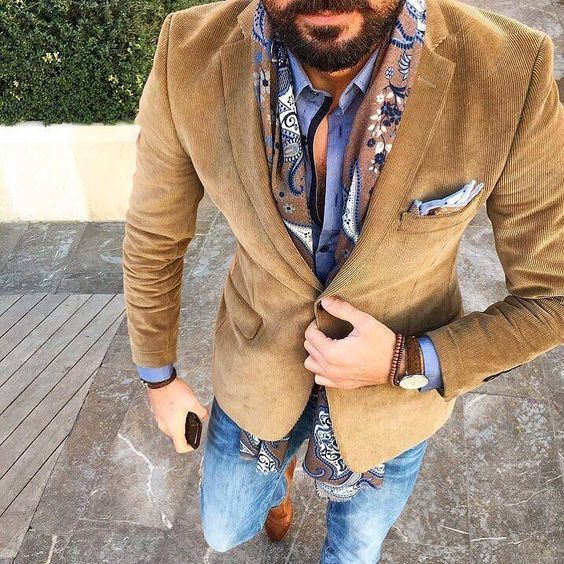 This combination of a brown corduroy sport coat and blue slim jeans is perfect for a night out or smart-casual occasions. Complement this look with brown suede loafers.   Shop this look on Lookastic: https://lookastic.com/men/looks/blazer-dress-shirt-skinny-jeans/24065   — Blue Dress Shirt  — Brown Paisley Scarf  — Light Blue Pocket Square  — Brown Bracelet  — Brown Watch  — Brown Corduroy Blazer  — Blue Skinny Jeans  — Brown Suede Loafers