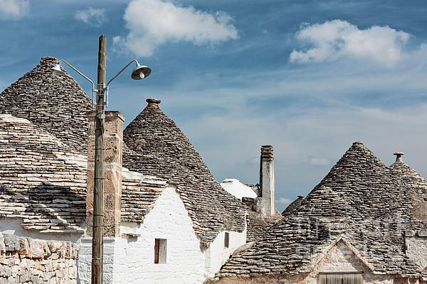 Typical rooftops of Alberobello houses under a blue sky, Puglia, Italy
