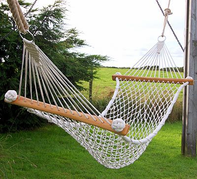 Hammock netted by hand in cotton with ash wood stays, in garden. I think I could make this. Esp. love the monkey fist side rope