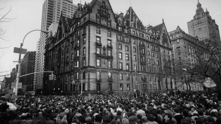 December 1980: Crowds gathering outside the home of John Lennon in New York after the news that he had been shot and killed. A flag flies at half-mast over the building